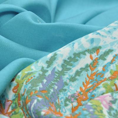 Вискоза ярко-голубого цвета с купоном на одной половине полотна из коралловых цветов