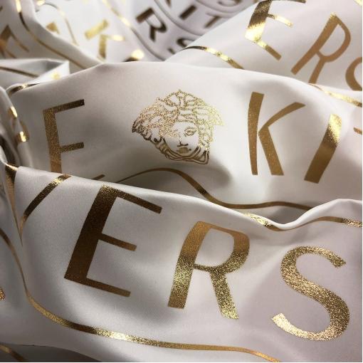 Ткань курточно-плащевая Versace молочного цвета с золотыми логотипами